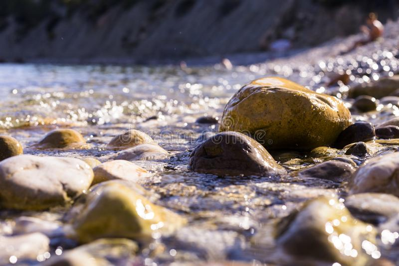 日落在海滩 水覆盖着岸上的岩石 背景人物 暑假 伊维萨 免版税库存照片