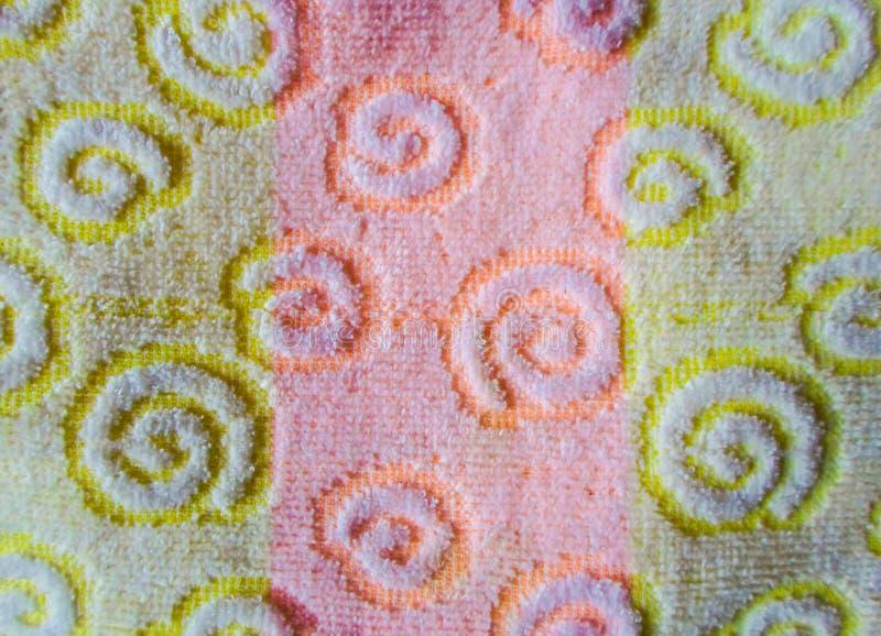 O tecido é amarelo e rosa muitos padrões na malha linhas verticais, padrão espiral fotos de stock