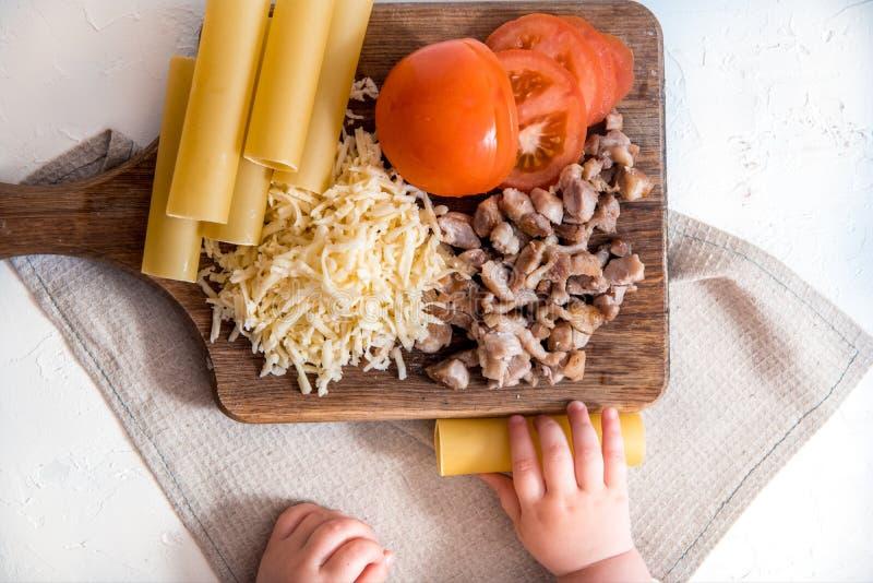 Chef-kok kokende spaghetti in de keuken kokende deegwarencannellonien ruwe deegwaren en bechamel saus op een witte achtergrond stock fotografie