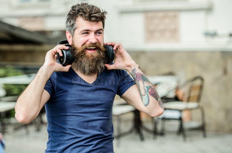 自由网上音乐来源 音乐是什么我是 耳机听的歌曲的英俊的有胡子的人 搜寻喜爱 免版税库存照片