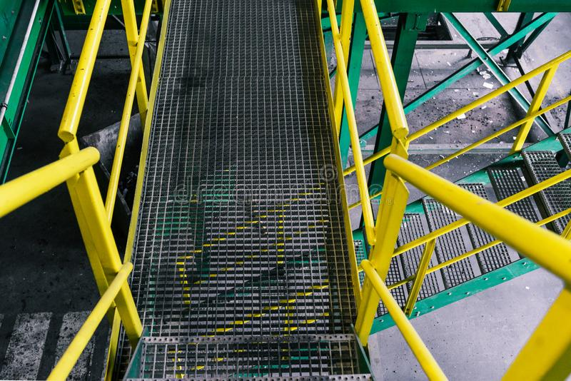 A escada metálica pintada em cores verdes e amarelas Escada de ferro numa fábrica ou fábrica industrial Garragem de metal no chão foto de stock