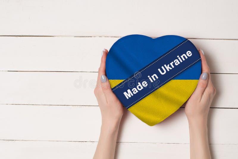 Inskrift som göras i Ukraina, flaggan av Ukraina Kvinnliga händer som rymmer en hjärta formad ask Vit trätabell på en bakgrund royaltyfri foto