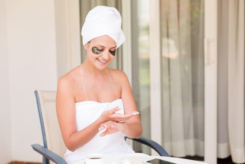 Garota feliz sorrindo mancha com creme de pele hidratante Mulher jovem aplicando creme de corpo Esfolamento de beleza e bem-estar imagem de stock royalty free