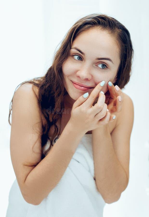 Młoda kobieta patrząca i ściskająca trądzik na twarzy przed lustrem Brzydka, problematyczna dziewczynka, nastoletnia dziewczynka  obrazy royalty free