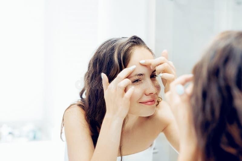 Młoda kobieta patrząca i ściskająca trądzik na twarzy przed lustrem Brzydka, problematyczna dziewczynka, nastoletnia dziewczynka  zdjęcie stock