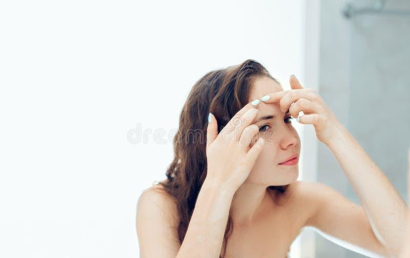 Młoda kobieta patrząca i ściskająca trądzik na twarzy przed lustrem Brzydka, problematyczna dziewczynka, nastoletnia dziewczynka  zdjęcia stock