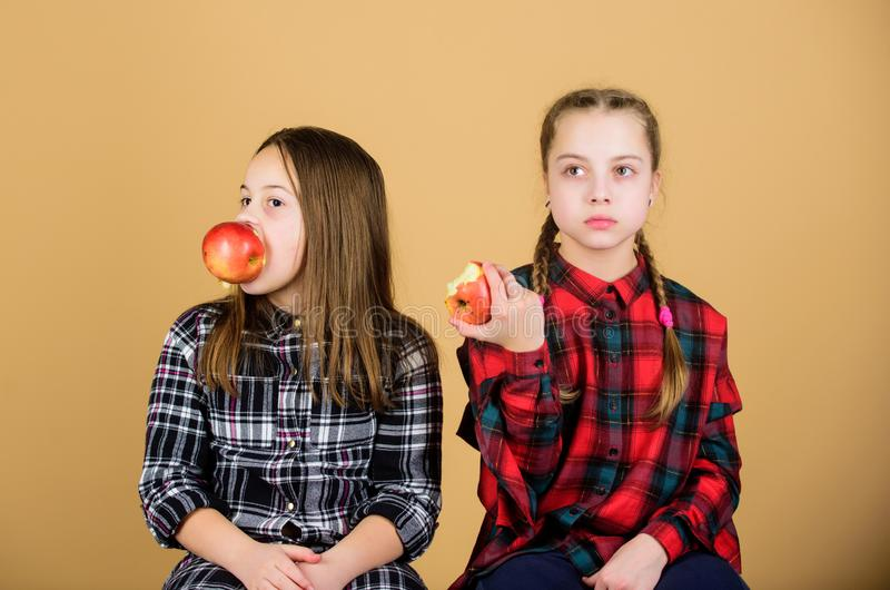 Mangia frutta per essere carina Piccole ragazze che mangiano mele insieme Le bambine amano la frutta fresca Le ragazze carine man fotografia stock