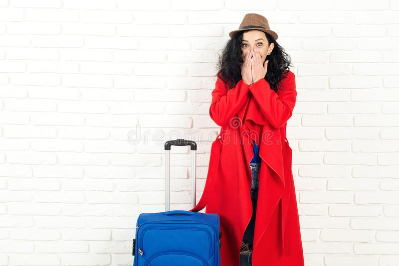 旅行梦 女孩不敢相信那会成功 时尚的女性,随时可以旅行 白墙上有行李箱的女孩,复制 免版税库存图片