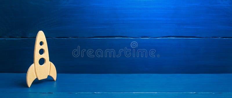 在蓝色背景的一枚木火箭 样式减速火箭 空间飞行和成就的概念在高技术 库存照片