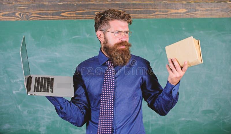 Учитель бородатый хипстер держит книгу и ноутбук Выберите правильный метод обучения Преподаватель выбирает современный метод преп стоковая фотография rf