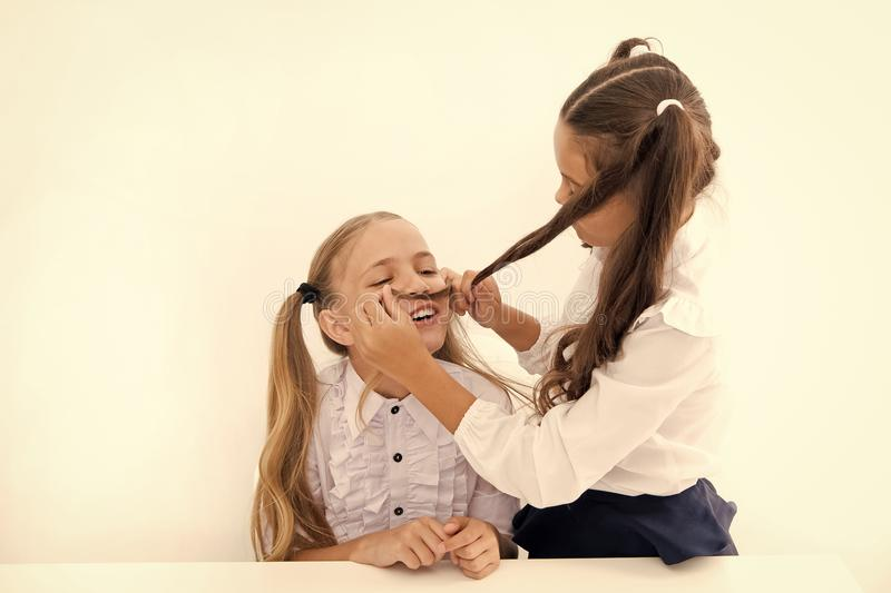 Девушки делают усик с длинными волосами Lets представить вас был мальчиком Игра настроения девушки жизнерадостная шаловливая с во стоковая фотография rf