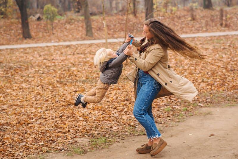 快乐家庭在秋园漫步 年幼的母亲在落叶中与儿子玩耍 妈妈在甩她蹒跚学步的儿子 家庭享受 库存图片