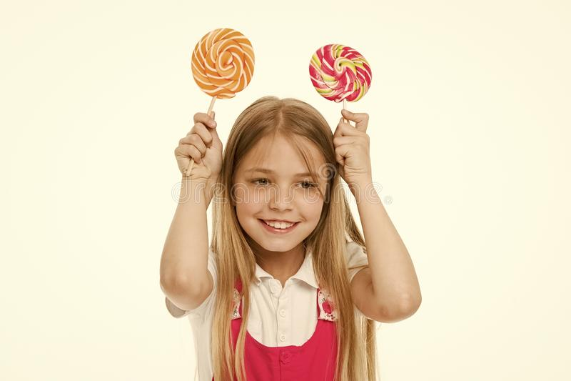 微笑用漩涡焦糖的滑稽的女孩 小孩微笑用在白色隔绝的棍子的糖果 甜和极端 免版税图库摄影
