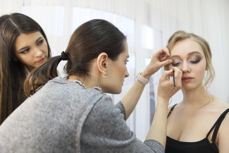 化妆老师和她的女学生 在美容学校补习 在她的工作室里画画 主类 免版税库存照片