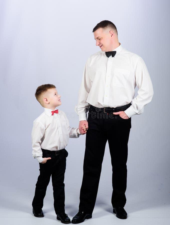Маленький сын следует примеру отцов благородного человека Воспитание джентльменов Посетите дресс-код театра Официальный отец и сы стоковое изображение rf