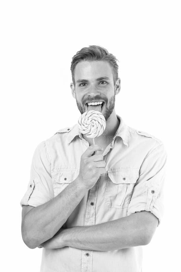 Γλείψιμο αυτό Όμορφος γενειοφόρος τύπος ατόμων που χαμογελά γλείφοντας την καραμέλα Ο εύθυμος φαλλοκράτης χαμόγελου τύπων αισθάνε στοκ εικόνα
