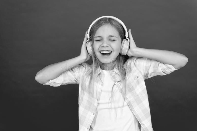 Музыка всегда со мной Маленькая девочка слушает наушники песни Онлайн канал радиостанции r Ребенок девушки стоковое фото