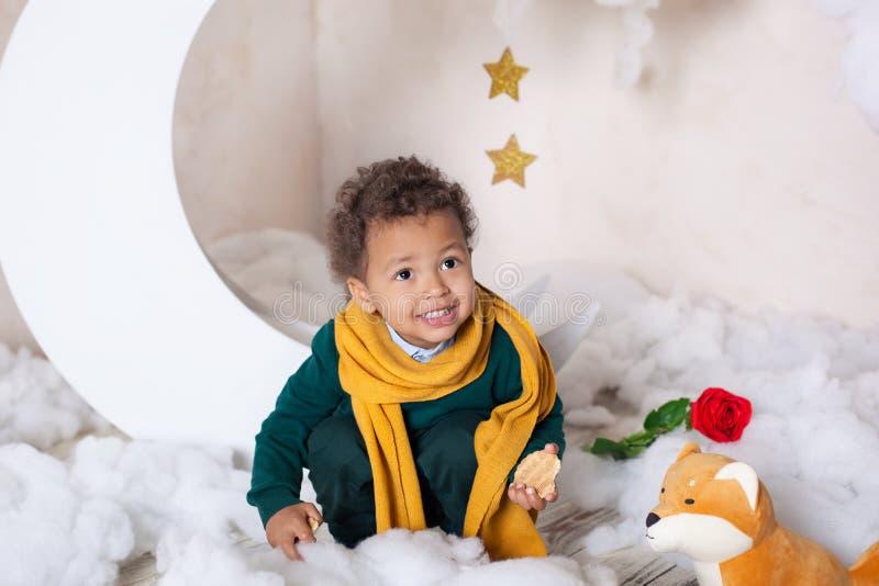 Черный мальчик в зеленом свитере и желтом усмехаться шарфа Портрет маленького афроамериканца Улыбки младенца Черный парень ребено стоковое фото rf