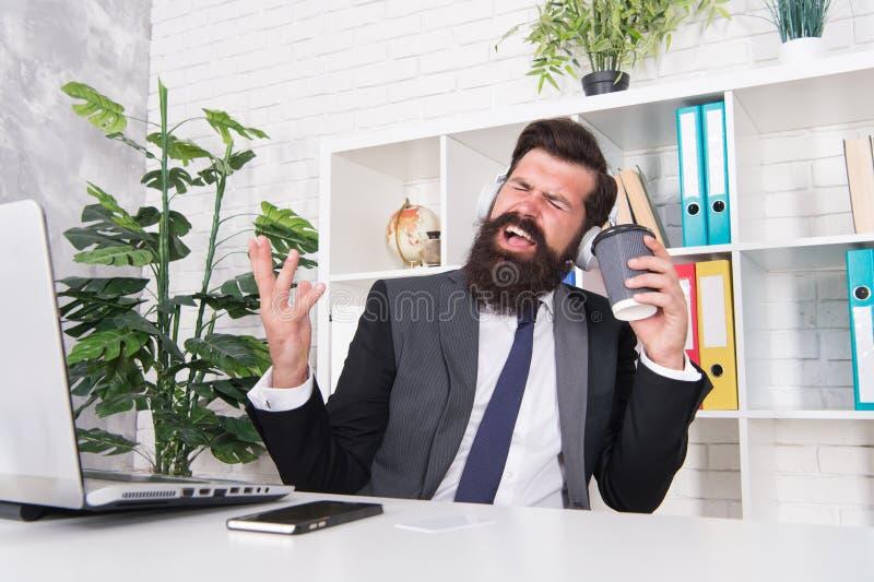 唱歌爱好 重音抵抗概念 放松用喜爱的音乐和杯子咖啡的经理 人办公室工作者 库存照片