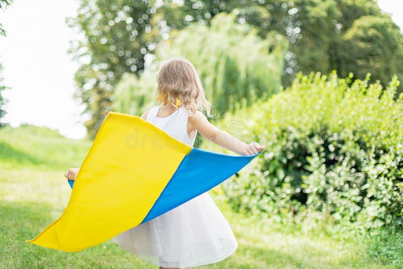 孩子运载振翼乌克兰的蓝色和黄旗领域的 乌克兰的美国独立日 国旗纪念日 宪法天 女孩i 库存照片