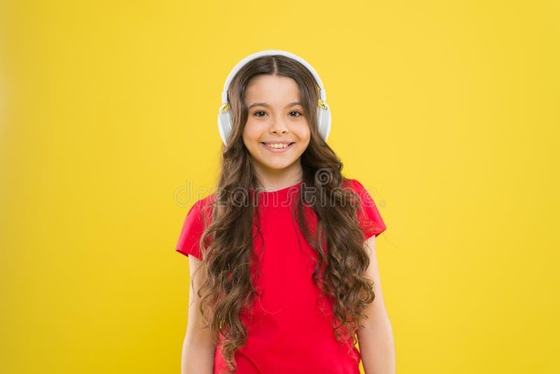 Άριστη ακουστική ποιότητα ήχου Τοπ τραγούδια Ο έφηβος παιδιών απολαμβάνει το παιχνίδι μουσικής στα ακουστικά Μικρό κορίτσι που απ στοκ φωτογραφία