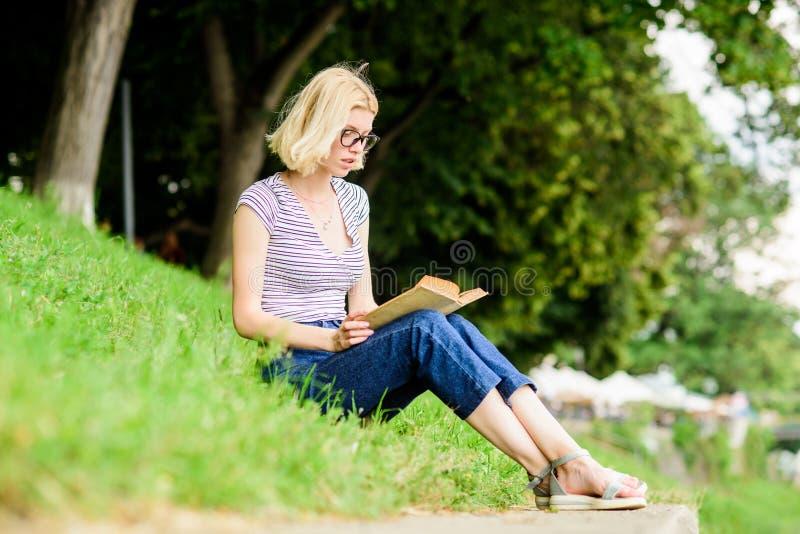 有趣的故事 放松并获取新信息 户外书籍 公园读书的女人 灵感 免版税库存图片