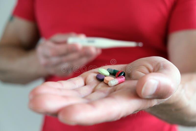 有一个温度计的一个人在他的手上 高的体温 冷和流感药片 预防和加强免疫 ?treadled 库存图片