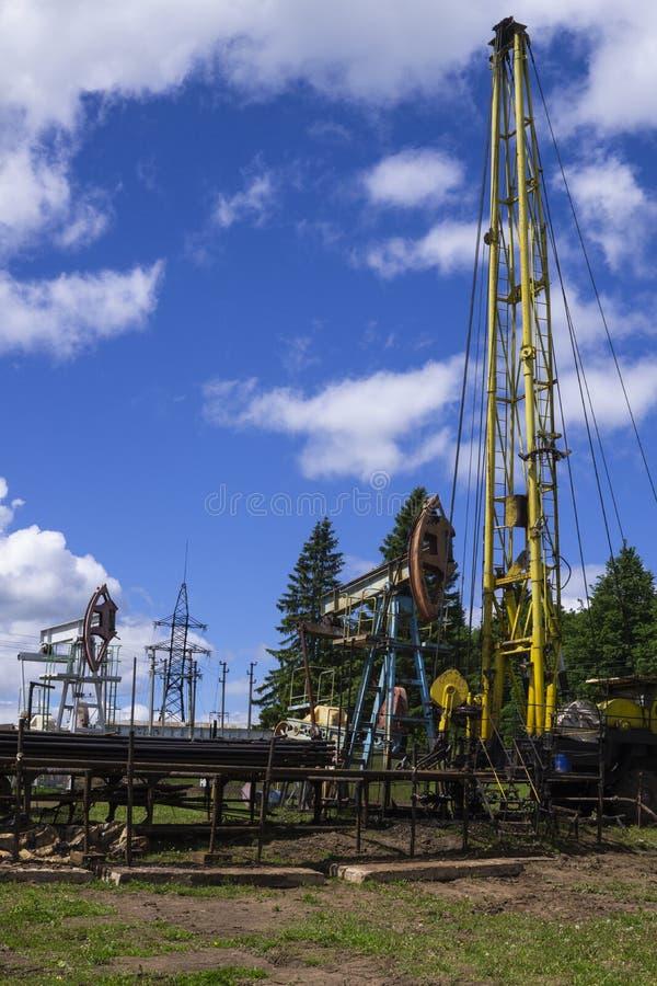 Pumpenheterna och brunnsdriften Oljepump Jack Sucker Rod Beam och Workover Rig Arbetar med oljekällan Olja och gas arkivbild