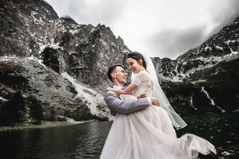 Hermosa sesión fotográfica de boda El novio rodea a su joven novia, a la orilla del lago Morskie Oko Polonia fotos de archivo libres de regalías