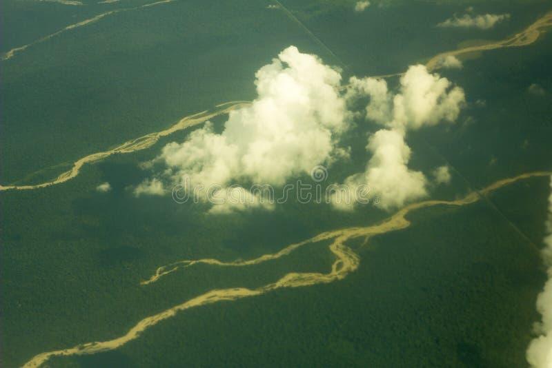 Piaszczyste łóżka rzeczne pośród zielonego lasu, widok z wielkiej wysokości białe chmury nad ziemią zdjęcia lotnicze obrazy royalty free