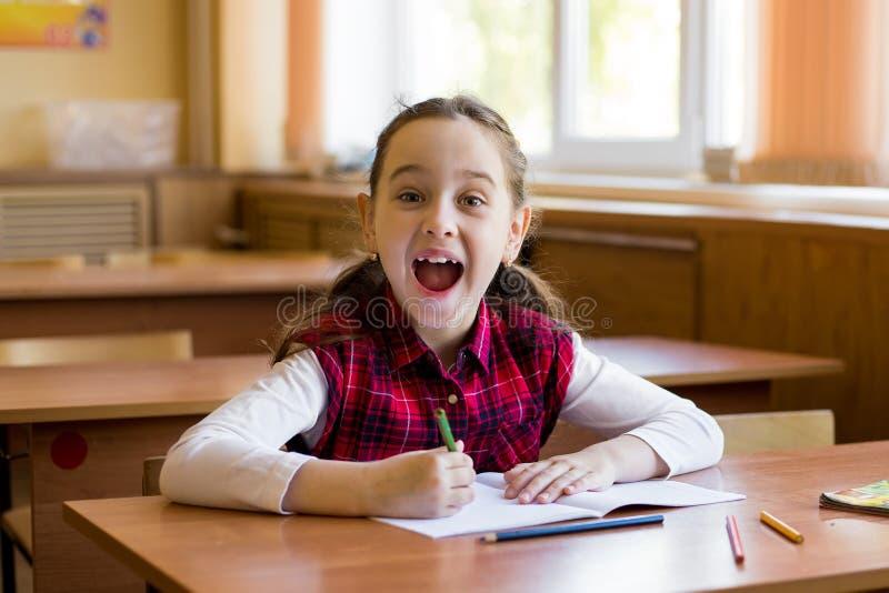 Niña caucásica sonriente sentada en el escritorio en la habitación de clase y grita alegremente Retrato de una joven preescolar F imagen de archivo