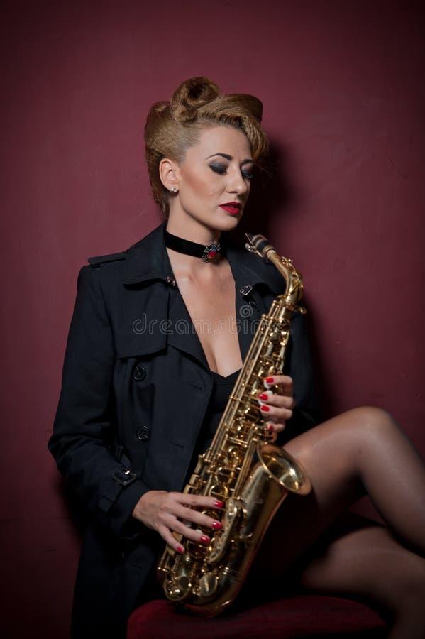 mulher atraente com saxofone a posar em fundo vermelho Jovem loura sensual jogando sax Instrumento musical, jazz imagens de stock