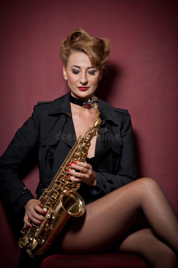 mulher atraente com saxofone a posar em fundo vermelho Jovem loura sensual jogando sax Instrumento musical, jazz foto de stock royalty free