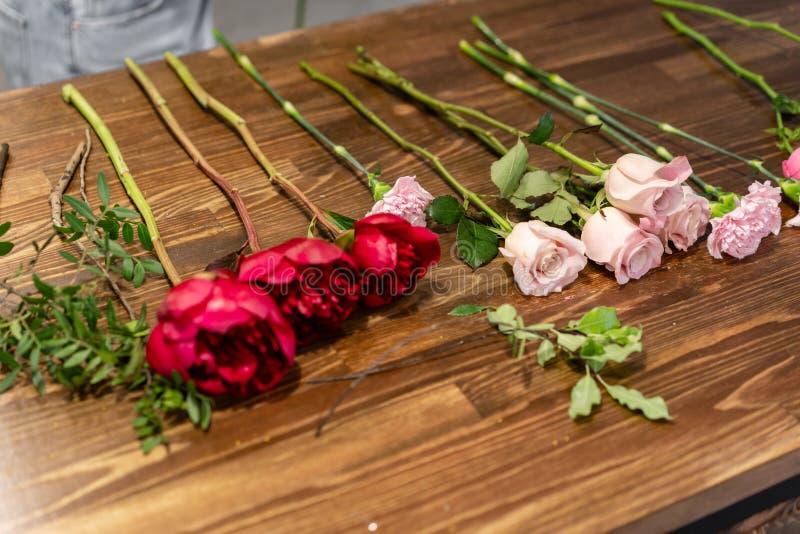 Conjunto de flores para um buquê na mesa O trabalho de uma turma florista de mestrado em fazer bouquets bouquet de Verão imagens de stock royalty free