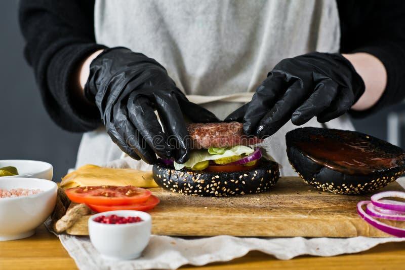 O chefe está cozinhando um cheeseburger O conceito de cozinhar um hambúrguer preto Receita de hambúrguer caseira foto de stock