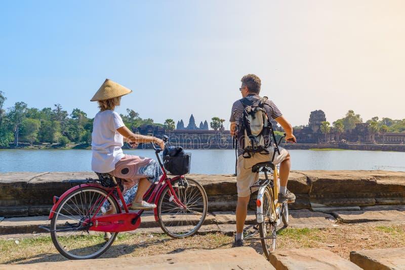 Turistparet cyklar i Angkor temple, Kambodja Angkor Wat main facade reflekterat på vattendammen Miljövänlig turism royaltyfria bilder