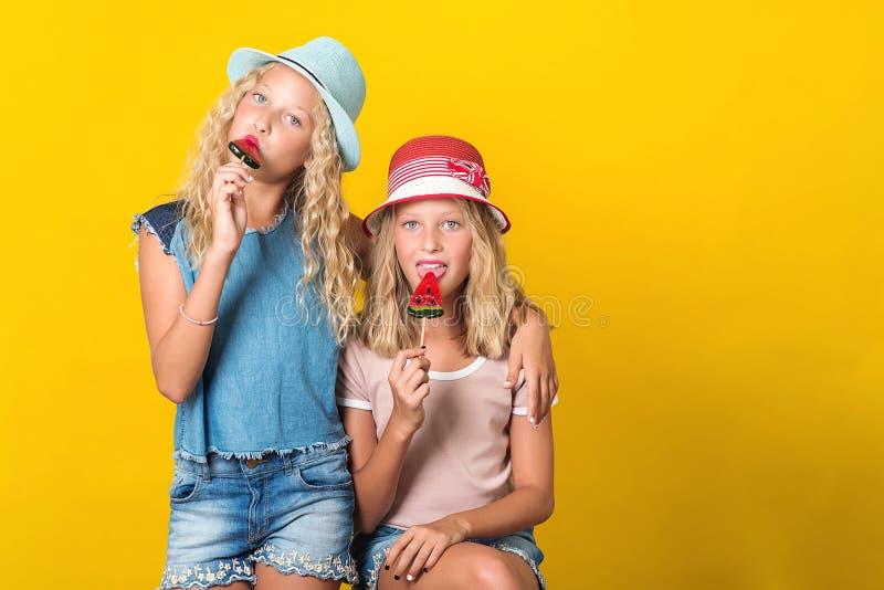 Glad tvillingsystrar på sommarhattar Tonåringar, flickor, med gul bakgrund Strålar i snygga sommarutrustningar Funniga flickor arkivbild