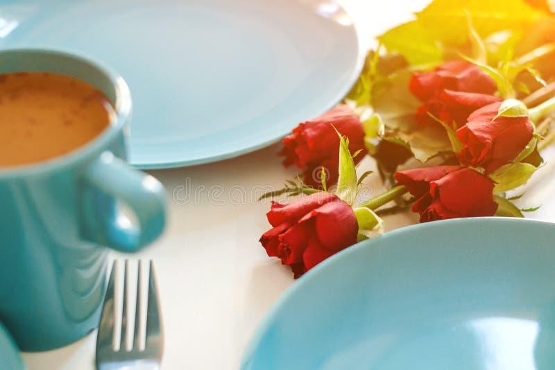 Morgonfrukost på köksbord Röda rosor och kopp kaffe med mjölk på bordet Romantisk frukost med blommor Alla dagar royaltyfri foto