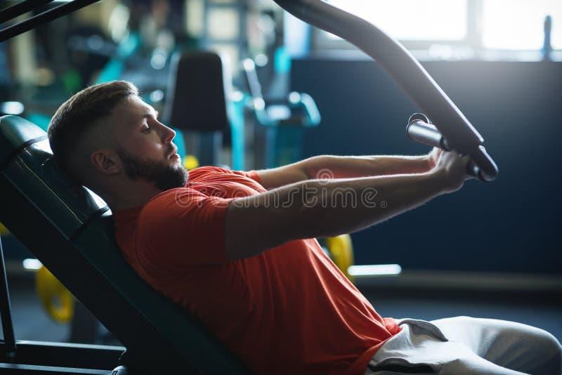 Homme musculaire établissant dur au gymnase Exercices de machine S?ances d'entra?nement de coffre photographie stock libre de droits