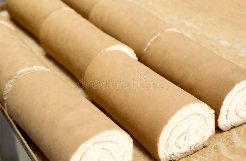 Keksrollen mit Füllung und Kondensmilch sind auf dem Tisch Bonbon und Rolle zum Nachtisch S??igkeitenproduktion lizenzfreies stockfoto