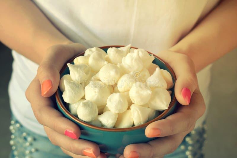 Mini- marängkakor Hemlagad maräng kysser droppar i blå bunke i flickahand s?t bakelse Gluten frig?r arkivbild