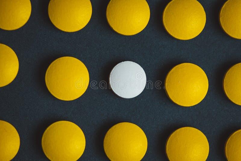 Einzigartige weiße Medizin-Pille unter vielen gelben Lassen Sie sich von einem Menschenmengen-, Individual- und Differenzkonzept  stockfoto