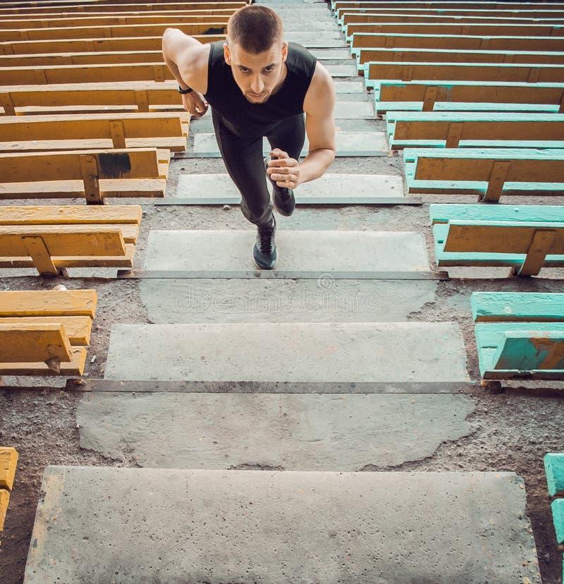 Kaukasische mantreinen op de trap Wandelende baan- en praktijkopleiding in de sport — uniforme opleiding buitenshuis atleet, bove royalty-vrije stock fotografie