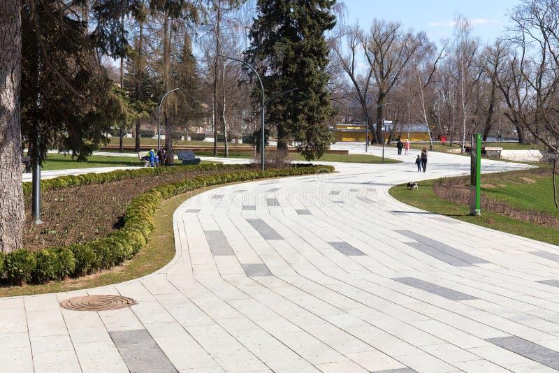 Winnende voetpaden in het stadspark van Moskou Burgers in het park Lente, troebel Stedelijk landschap De VDNKH royalty-vrije stock fotografie