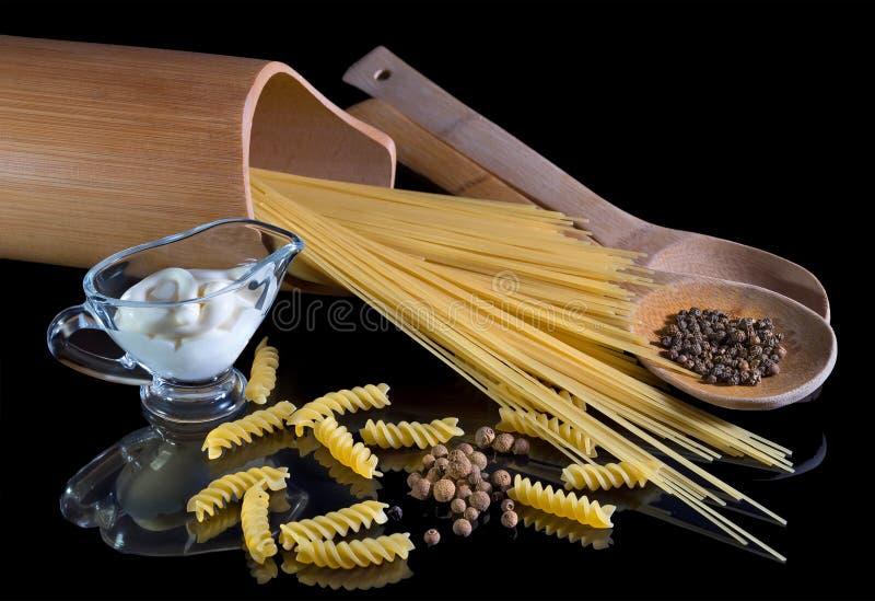 Pâtes italiennes jaunes, spaghettis, poivre noir sur fond noir isolé. Une belle vie morte. Gros plan photos stock