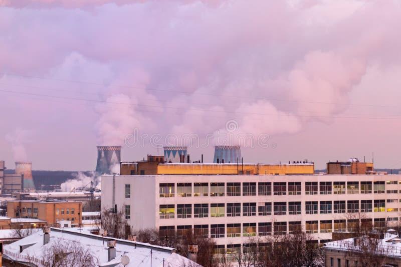 Paysage de la ville à l'aube, lever de soleil avec belle horizon, bâtiments. cheminées fumantes d'une entreprise industrielle.  image stock