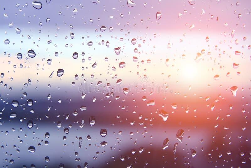 Vattendroppar på fönsterglas efter regn med dramatiskt suddigt solnedgång i bakgrunden Infärgat flytande bakgrundsmaterial Väder royaltyfri bild