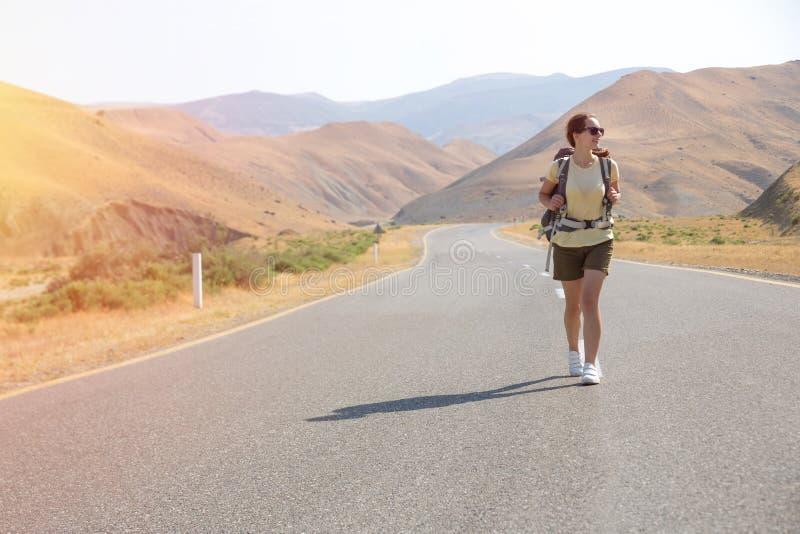 Mujer del viajero del autostopista en el camino en puesta del sol Caminante del viajero de la muchacha en el camino Vacaciones de imagenes de archivo