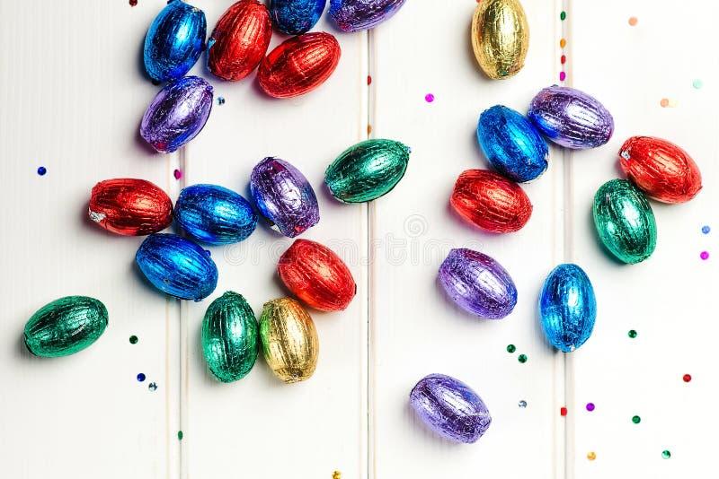 Uova di cioccolato pasquale in fogli colorati su sfondo bianco Sfondo Pasquale Vendite di Pasqua Buone vacanze di Pasqua fotografie stock