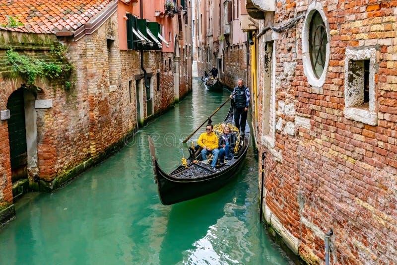 Un homme et une femme du Caucase souriant couple de touristes en gondole Gondolier debout derrière Venise, Italie photo stock